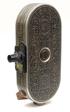 Bell & Howell Filmo - 1928, designed to be a portable movie camera suitable for amateur use.  It weighed 3 pounds and could fit in a coat pocket.  You'd wind it like a watch with a permanently attached key that fit into the side of the camera.  It cost as much as a car.