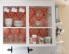 I love this redo - remove doors, apply patterned paper or fabric, then paint cabinets white.