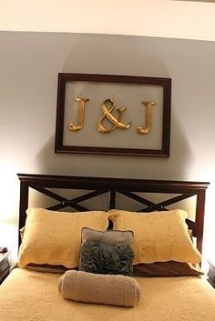 initials above the bed in an empty picture frame