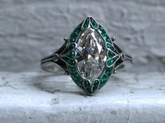 I LOVE this piece soooo much I am seriously wondering why I am selling it! This Vintage Art Deco Platinum Navette Emerald and Diamond Ring Engagement Ring is just stunning. Crafted in Platinum, the design features an amazing Marquise Cut Diamond in the center, with a gorgeous Cabochon Natural Emerald Halo Surround, and finished with lovely Beaded Edges and Art Deco Shoulders. In the center, the ring holds One Marquise Cut Diamond, approximately 1.85ct, of K/I1 quality. Surrounding are 31...