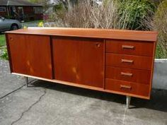 Vintage teak veneer sideboard - 70.5 inches long, 18 deep and 30 high - four drawers and a pair of shelves behind two sliding doors - the stainless steel legs can be adjusted to short and lengthen adding or subtracting a few inches from the height - dugout handles - stripped and refinished with danish oil.