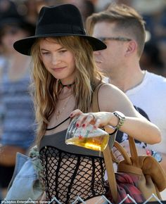 No thank you: The glamorous girl was pictured tipping away her beer after sampling it ...