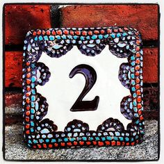 Hand made ceramic house number tile with deep chocolate brown background and highlighted in orange, teal, and light blue. Works well for 1