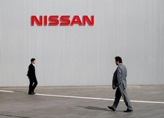 Men walk past a Nissan Motor Co logo at the company's global headquarters in…