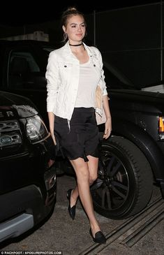 Chic: Kate Upton showed off her slim legs in a black skirt teamed with a white top as she ...