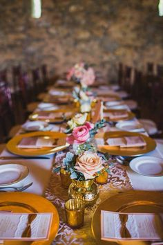 This outdoor rehearsal dinner included pushed together farmhouse tables that were covered in gorgeous pale pink and orange garden roses and vintage runners from the groom's home country of India.