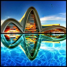 Wavy design of the building and the reflection of the pool makes it similar to sound waves or natural waves that blend in with the water around the building.