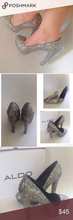 Aldo Passarello Silver Pumps Authentic new with box. Get pretty in the Passarello. ALDO presents a glam silhouette with silver rock glitter and rounded toe. You'll shine with every step taken in the 5 1/2 inch block heel and 1 inch platform. Product Features: Almond-toe pump featuring in allover glittery sequins featuring chunky platform and heel. Women's Size 9. Note that this is a display pair and may show minimal signs of wear from being tried on and displayed at the store. Aldo Shoes…