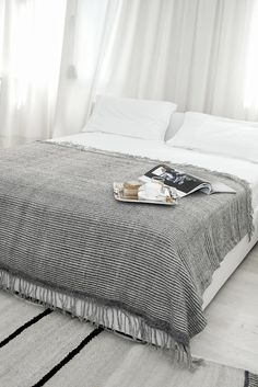 When you start with white bedding, it only takes a few small touches (like a grey throw) to change it up