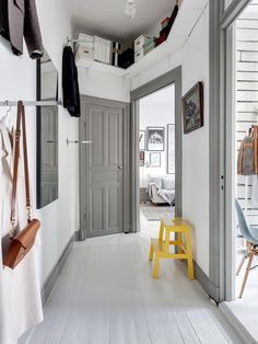 Grey & white hallway with bright yellow stool as accent piece Grey Interior Doors, Grey Doors, Grey And White Hallway, White Walls, Decoration Hall, Gravity Home, Hallway Designs, Grey Trim, Dark Trim
