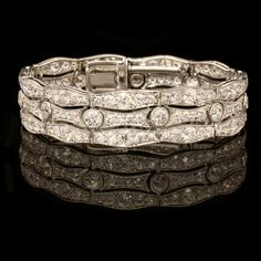 An art deco platinum and diamond bracelet by Cartier c.1925 -The bracelet designed as three undulating rows of transition cut diamonds, the two outer rows each with eleven articulated uniform convex shaped motifs, grain set with five graduated diamonds in a platinum millegrain setting - The central row with eleven concave links alternating with a single rub over set diamond, all to a concealed tongue and box clasp. - L:16,2 cm