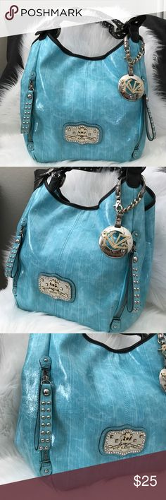 KATHY VAN ZEELAND Spa Blue Purse Perfect color to jazz up your Spring or Summer outfit !! This beautiful KVZ bag is a light spa blue with black straps featuring grommets, studs and buckles. Comes with classic KVZ hang tag. Lots of room inside. As pic shows there are a few small discoloration marks on some parts of the bag but not noticeable unless you look closeup. Gently used a few times. Kathy Van Zeeland Bags Shoulder Bags