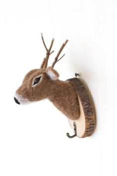 """This adorable dear comes to life with soft felt, twig antlers, and a natural wooden plaque base. Hang this little guy up for fun and easy wall storage piece, perfect for the kid's room! Gastonthe Woodland DeerMeasures 5"""" x 5"""" x 8"""""""