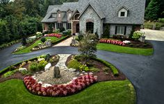 Large estate landscape design and build.  Long tree-lined driveway leading to a circular driveway with water feature center piece.