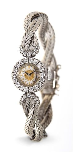 An 18 Karat White Gold and Diamond Wristwatch by Buccellati,  containing 32 round brilliant cut diamonds weighing approximately 0.84 carat total, 15.50 mm case diameter, two tone textured yellow gold and polished white gold dial in a sunburst pattern, applied yellow gold baton numerals, black index hands, diamond set bezel and lugs, case sidewalls accented with intricate floral motif engraving, snap on case back, 17 jewel Swiss movement.  Case back stamp: 18K. (=)
