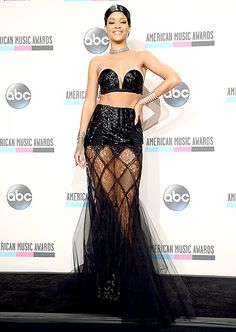 Rihanna bared her midriff in a black top and skirt with a sheer panel overlap that revealed her famous legs at the 2013 American Music Awards.