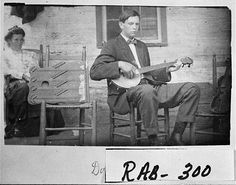 Rabun County, ca. 1920. Dock King sitting on the porch playing his banjo. At the left is Mrs. A. B. Forrester. Note the other string instrument on the chair at the left.