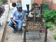 "Gonçales Mabunda, an artist for CCM's TAE program that turns decommissioned weapons into artwork, poses by his ""throne."""