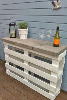 """Un palet puesto """"de pie"""" y asegurado a la pared con escuadras de metal sirve de base para una pequeña consola que hace las veces de mueble-bar. Esta y tres ideas más para terrazas y jardines en www.reciclatusmuebles.com"""