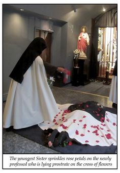 The youngest Sister sprinkles rose petals on the newly professed, who is prostrate on the cross of flowers