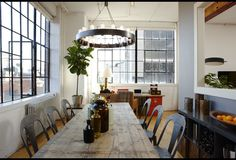 Cool Bachelor Loft - Industrial feel; large, round chandelier, rustic table, old metal chairs, gray accent wall, wood beam.