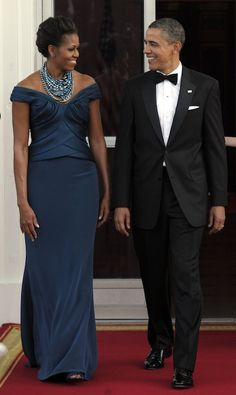 Michelle Obama  This accomplished beauty loves fashion. Her dress choice here highlights her long shape to advantage, and her famously toned arms too, of course. The dusky teal color compliments her lovely cocoa skin tone without being brash. This necklace is typically huge and spot-on.