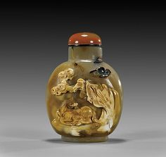 Finely hollowed, carved cameo agate snuff bottle; of rounded form: the front with design of horse resting beneath rockery and pine tree in relief rendered from the opaque suffusions; with red agate stopper; H: 2 7/8""