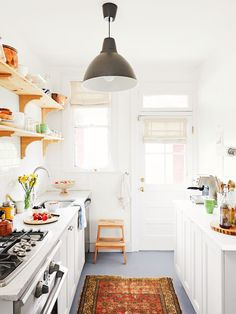 Tips and tricks to maximize your small galley kitchen. These ideas will make kitchen space larger and more functional. The two parallel counters of galley kitchens mean focusing on aisle space, light and storage. For more kitchen ideas go to Domino. Wood Floor Kitchen, Kitchen Flooring, Kitchen And Bath, New Kitchen, Kitchen Decor, Kitchen Cabinets, Kitchen Ideas, Ikea Cabinets, 1950s Kitchen