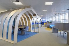 Office with similar lighting and ceiling to our office, changes in floor finish used to mark out spaces, creative bespoke joinery items to create meeting pods