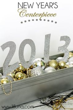 New Year's Centerpiece  Plastic Planter Box   Rustoleum Metallic Spray Paint   Floral Foam  Silver & Gold Christmas Ornaments  Silver & Gold Beaded Necklaces  Chipboard  Mod Podge  Glitter  Skewers