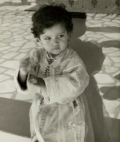 Young Princess Lalla Miriam, daughter of King Hassan II of Morocco, standing in tiled courtyard, playing with hands in 1964.