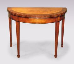 A good quality late 18th Century Sheraton period half-round satinwood Card Table, boxwood & ebony strung, having tulipwood & padoukwood double crossbanded top above ebony line-inlaid frieze supported on ebony line-inlaid square tapering legs ending on spade toes. Circa: 1790 Ref: 5075