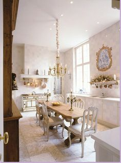 Without the pot rack, it would be hard to actually see this is a kitchen. The French stove looks like a jeweled box with ormolu. The light fixture plays off the brass of the range. Beautiful!
