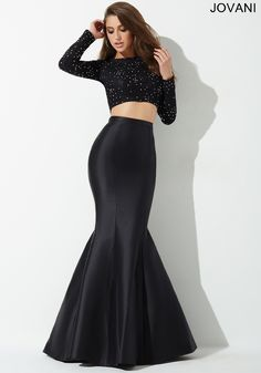 Gorgeous two-piece prom dress features a crystal embellished long sleeve top and poly-satin mermaid skirt
