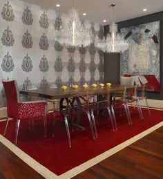 Red Dining Room, silver wall paper, double chandeliers, acrylic chairs. Artistic Designs for living.