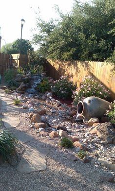 Backyard landscape - disappearing stream into a dry creek bed, stone pathway and native plantings.