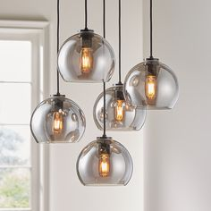 Shop Arren Black Round Pendant with Silver Round Shades. Arren suspends five silver glass shades from an iron fixture finished in black, the spherical pendants hanging from a circular ceiling plate and adjustable black fabric cords. Dining Room Light Fixtures, Kitchen Lighting Fixtures, Dining Room Lighting, Home Lighting, Modern Lighting, Club Lighting, Pendant Lighting Over Dining Table, Round Light Fixture, Outdoor Lighting