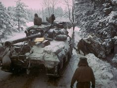 Battle of the Bulge. American Sherman M4 tank moves past another gun carriage which slid off icy road in the Ardennes Forest during push to halt advancing German troops, December 20th, 1944