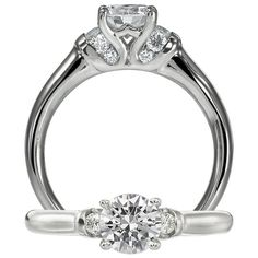 Modern diamond engagement ring featuring a prong set round cut diamond centerstone set within a royal crown design. Beautifully accenting this piece are the graduated diamond channel set shoulders.