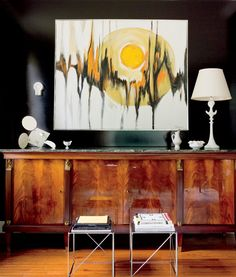 An oil painting by Tom Hayward hangs over an André Arbus cabinet in the home office, which is dramatically painted in Farrow & Ball's Pitch. Interior Design - Raji Radhakrishnan, Raji RM & Associates