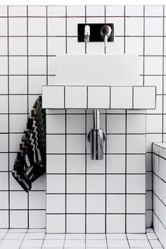 In the bathroom of the Bellevue Hill Apartment,  Dominic Kuneman added white gridded tiles with black grouting to cover the walls and floors.