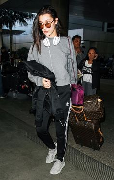Bella Hadid wears a sweatshirt, Adidas sweatpants, Yeezy Boost sneakers, a Chanel shoulder bag, and mirrored sunglasses