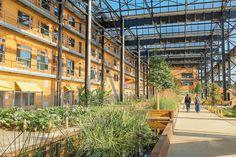Une structure métallique chapeaute les bâtiments en bois de l'ancien entrepôt, témoignage de l'histoire sociale et industrielle parisienne.