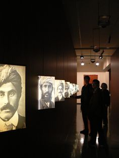 Immigration Museum, Melbourne - narrow entrance with black and white portraits, back-lit, stories on the back of the image