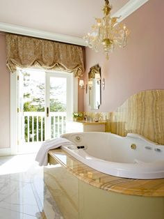 This master bathroom is a luxurious retreat contrasting classic tile and fixtures with vintage lighting and rich color. The centerpiece of the room is the oval jacuzzi tub with a stunning chandelier overhead. The tile, counters and flooring are crema marfil marble with honey onyx accents.