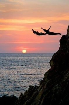Ballet style tandem cliff diving with a partner off the rock face in Alcapulco, Mexico as the pink sun sets under purple clouds that reflect the color onto the ocean. -DdO:) http://www.pinterest.com/DianaDeeOsborne/universe-lights