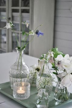 fresh flowers in old bottles, grouped on a tray