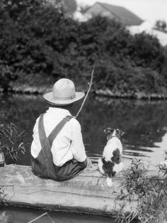 1920s 1930s Farm Boy Wearing Straw Hat And Overalls Sitting On Log With Spotted Dog Fishing In Pond Photographic Print