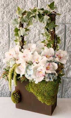 Dozens of white Orchids carefully arranged in a unique, moss-covered wooden box…