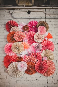 DIY paper pinwheel wall behind our wedding dessert table -  by The Party Dialect - coral, peach, orange, raspberry, and pink paper pinwheels.  Paper rosettes.  Pinwheel backdrop.